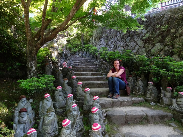 Julie with the be-hatted stone figures at the Daisho-in temple at the base of Mount Misen