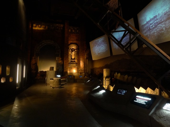 The first room of the Nagasaki Atomic Bomb Museum. Wreckage of destroyed buildings and screens showing photographs of the aftermath makes a powerful first impression
