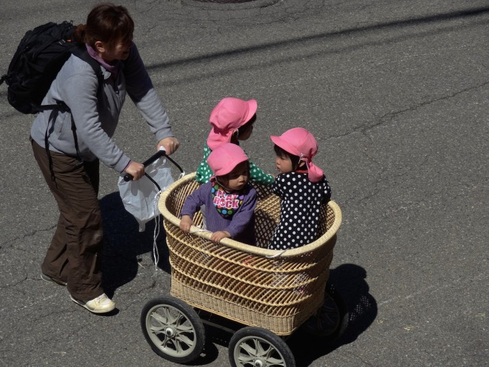Woman pushing a wicker basket trolley of toddlers