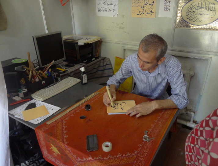 Calligraphy teacher writing Julie's name in Arabic. He explained that he travels quite a bit to advise the decorative restoration and construction work of Islamic buildings within Uzbekistan