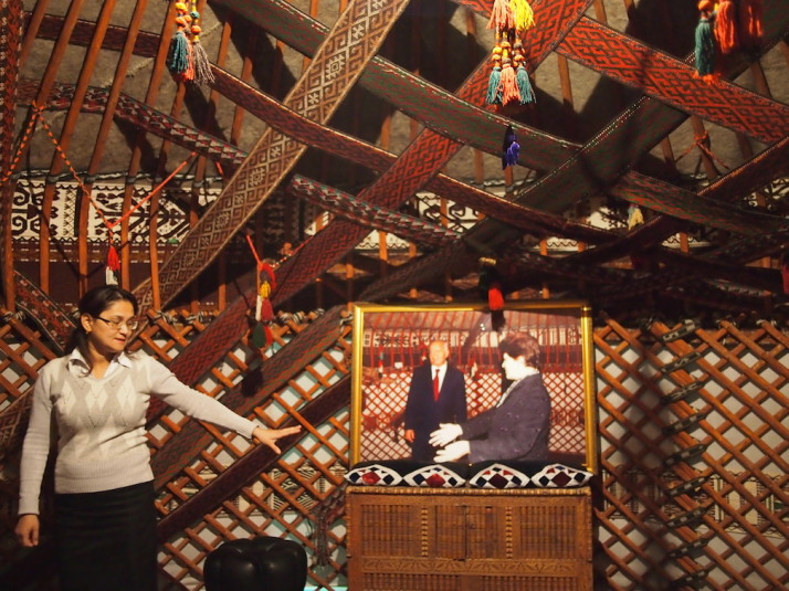 Ays, our guide, explaining about the central chest of the museum's 6-wall yurt. The photo is of Uzbekistan's President Islam Karimov with the current Director of the museum, Marinika Babanazarova