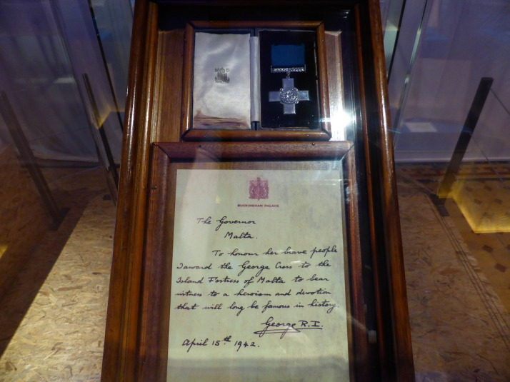 "The George Cross for Gallantry awarded to the people of Malta and which adorns the nation's flag. The accompanying letter reads: ""The Governor, Malta. To honour her brave people I award the George Cross to the Island Fortress of Malta to bear witness to a heroism and devotion that will long be famous in history. George R.I. April 15th 1942"""