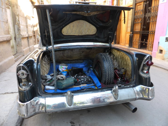 Inside the boot of a classic 1950's American car in Old Havana, propped open and full of tools