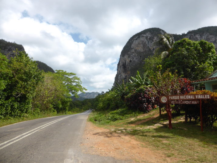 Viñales national park entrance, a road heads off into the distance between two large limestone karsts