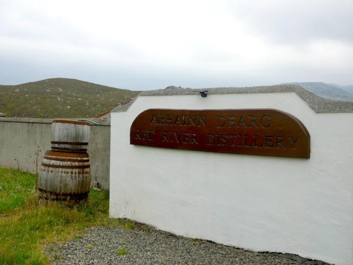 Abhainn Dearg (Red River) distillery sign board and 2 whisky barrels