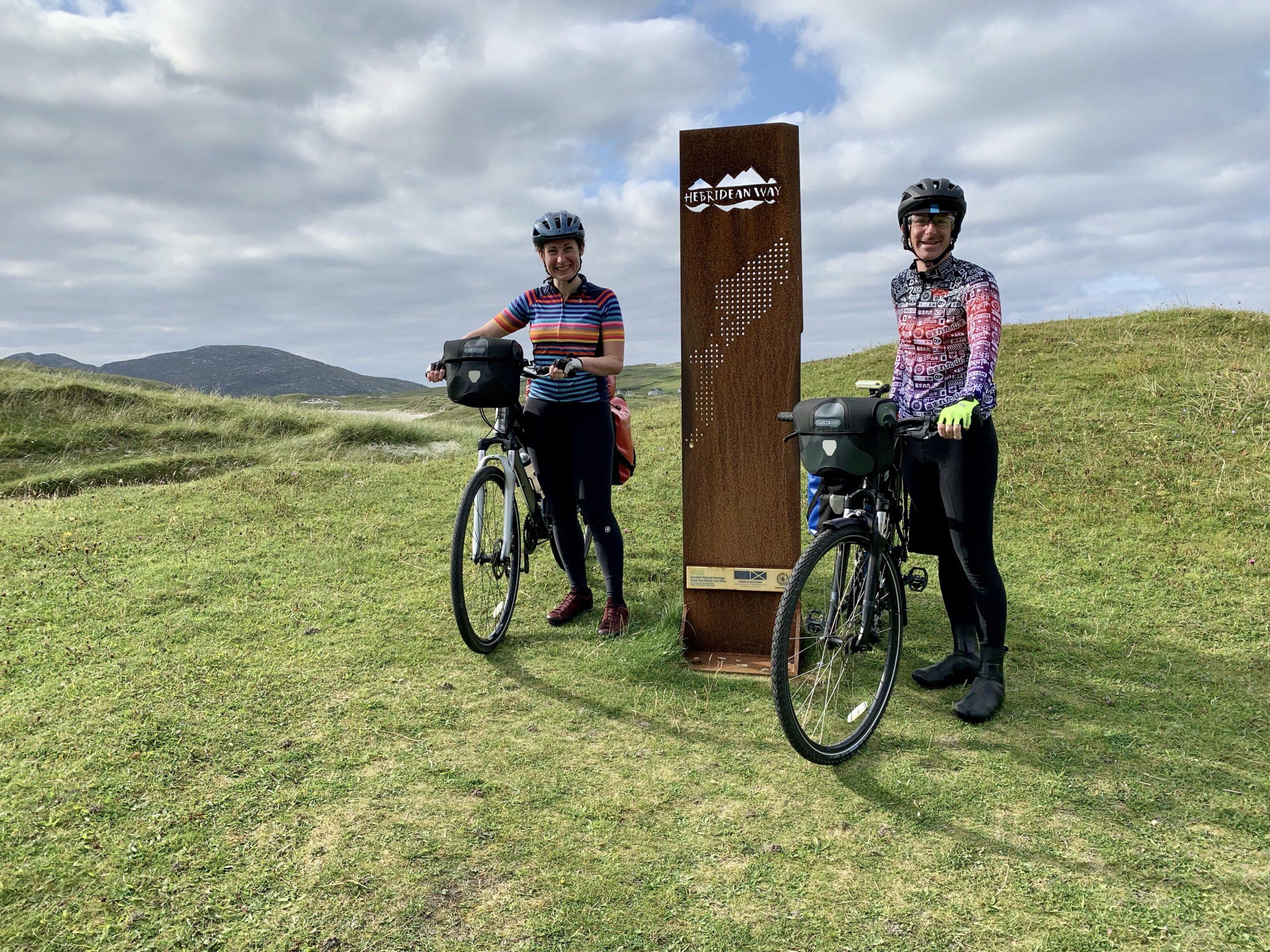Cyclists at the sign marking the start of the Hebridean Way on Vatersay